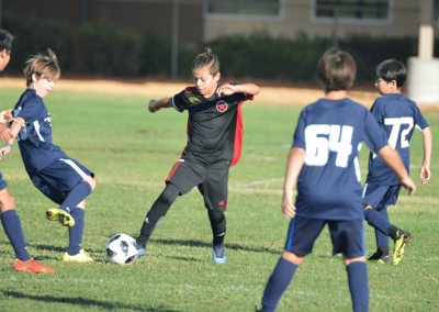 Youth boys soccer player dribbles the ball with his right foot