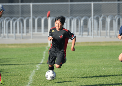 Youth boys soccer player runs after a ball