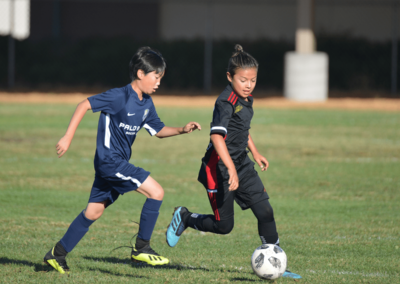 Boys soccer player dribbles the ball past a defender