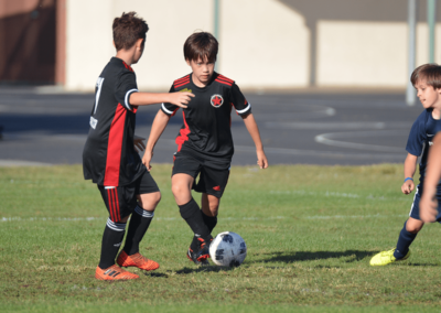 Boys soccer player passes the ball to a teammate