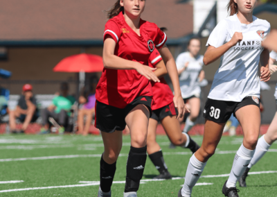 Red Star soccer player dribbles the ball past a defender