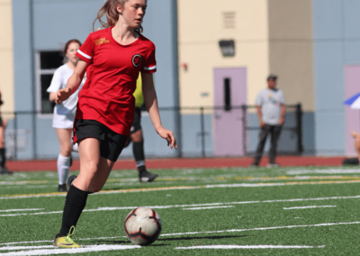 Woman dribbles the soccer ball wearing a Red Star Jersey