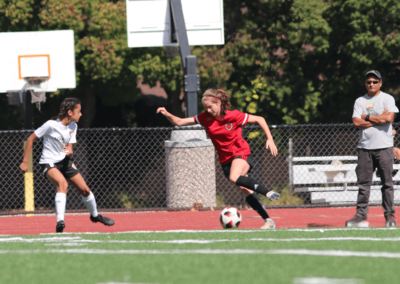 Girls soccer player in red dribbles the ball